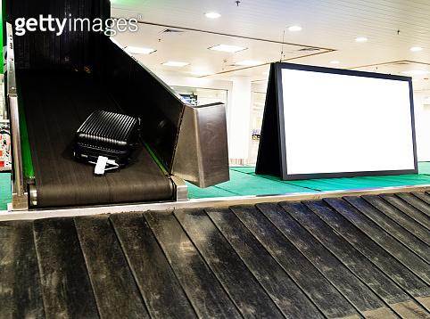 Billboard next to baggage conveyor belt