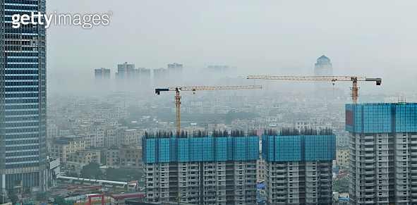 Modern skyscrapers under construction in foggy day