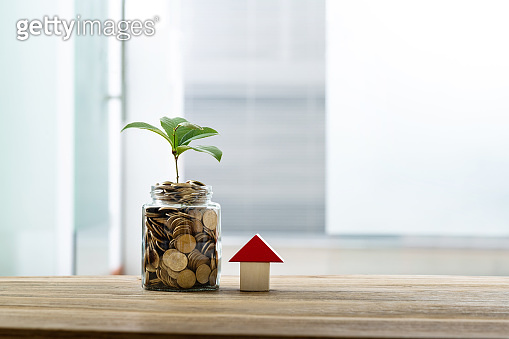 Glass coin jar and house model on the table