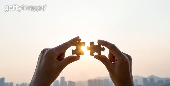 Woman hand putting puzzle pieces together in sunset