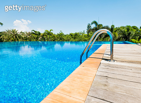 Swimming pool with ladder under blue sky