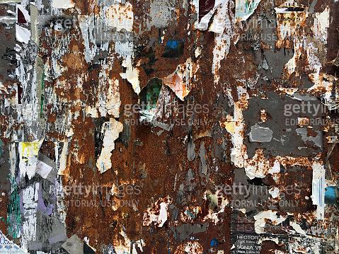 Torn paper over rusty metal