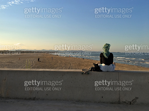 Young woman with dyed green hair contemplating the sea