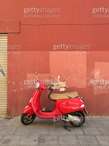 Red motor scooter parked on the sidewalk