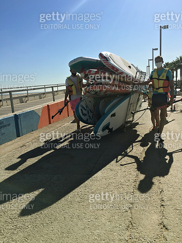 Surf instructors carrying tables during the COVID-19 pandemic