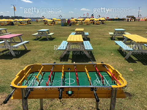 Foosball table outdoors next to wooden tables