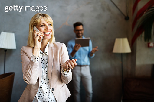 Happy beautiful businesswoman talking on the phone in office.
