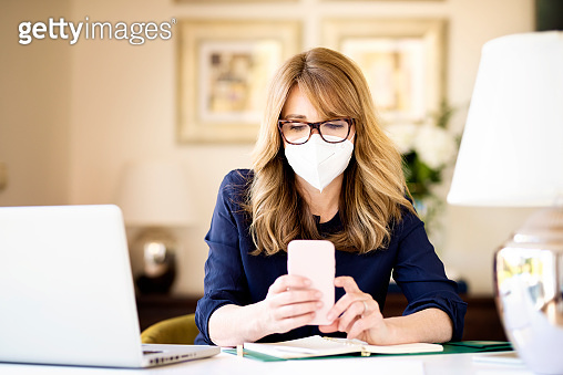 Middle aged woman wearing face mask for prevention while working from home