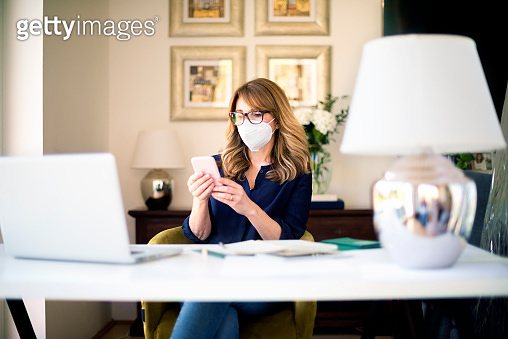 Mature woman wearing face mask while working from home during coronavirus pandemic