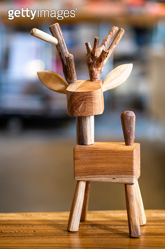 Cute wooden deer model on the table for Christmas decoration with blurred background.