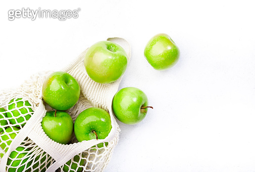 Organic green apples in reusable eco-friendly string mesh bag. Zero waste, plastic free and sustainable lifestyle concept. White kitchen table background, copy space, top view