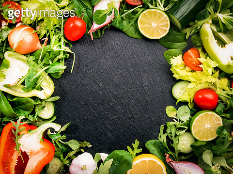 Healthy food background with various green herbs and vegetables. Ingredients for cooking salad. Vegetarian and vegan food concept. Top view, copy space