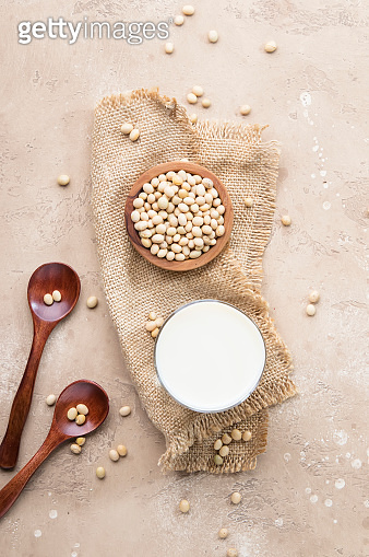 Soy milk and soy bean on beige background. Alternative Non-dairy milk concept. Vegan Beverage. Copy space
