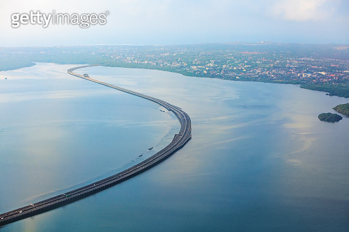 Aerial view of Bali Mandara toll road over sea gulf