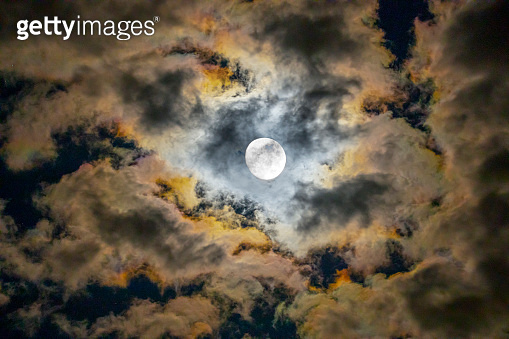 Full moon shows through opening in dark night clouds.