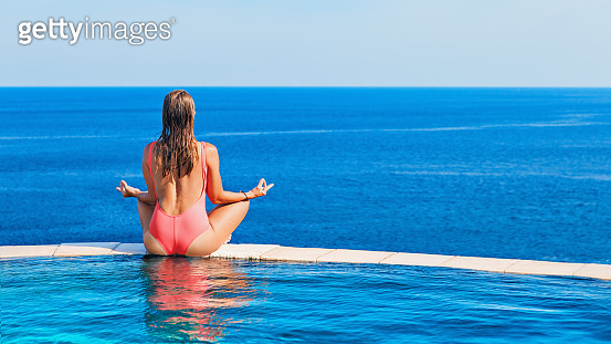 Woman at edge of infinity swimming pool with sea view.