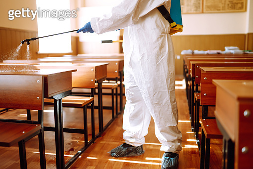 Man wearing protective suit disinfecting school class with spray chemicals to preventing the spread of coronavirus, pandemic in quarantine city.