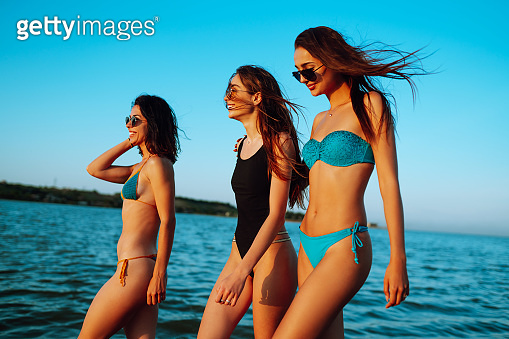 Beautiful three girls strolling along a beach.