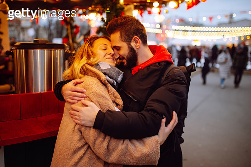 Young  couple outdoors at winter on a new year`s eve having fun at a winter fairy, lights all around, souvenir shops.