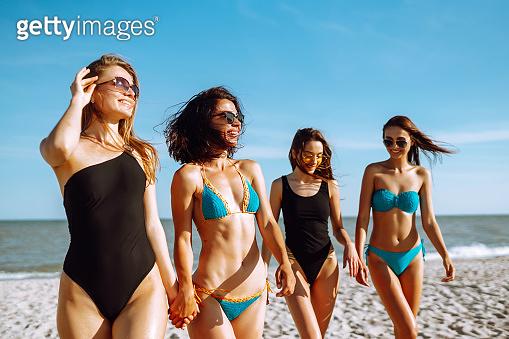 Happy four girls strolling along a beach.