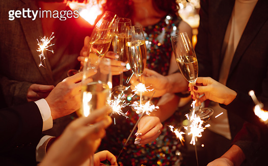 Glowing sparkles in hands. Group of happy people enjoying party with fireworks. Winter holiday, youth, lifestyle concept.