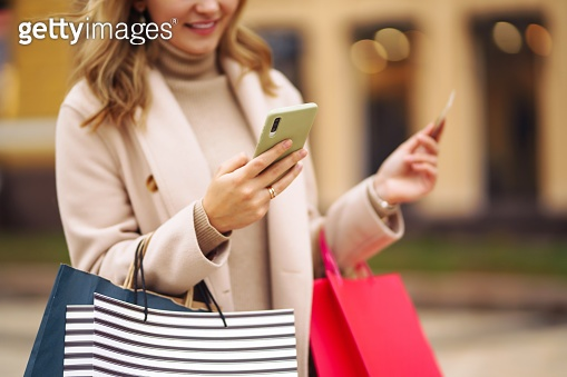 Hands of beautiful woman with telephone and a credit card. Online Shopping.
