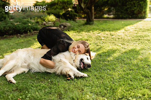 Woman playing with dog Labrador outdoors. Friendship of people and animal
