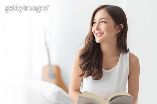 Pretty Charming Young Woman sitting smiling looking out at bedroom in the morning. Relaxed Beautiful female enjoying at home. Cheerful Asian girl reading book in white room. Healthy Lifestyle, Holiday