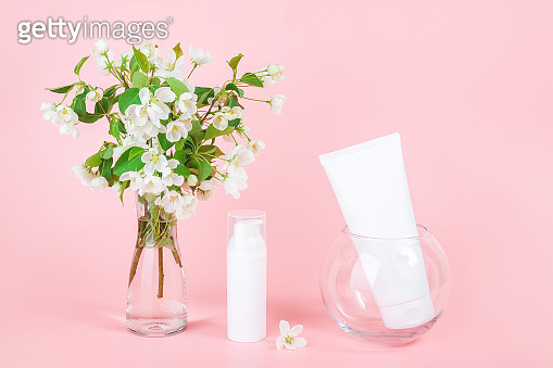 White blank cosmetics tube and bottle and apple blooming branch in vase on pink background. Natural Organic Spa Cosmetic Beauty Concept. Mockup Front view
