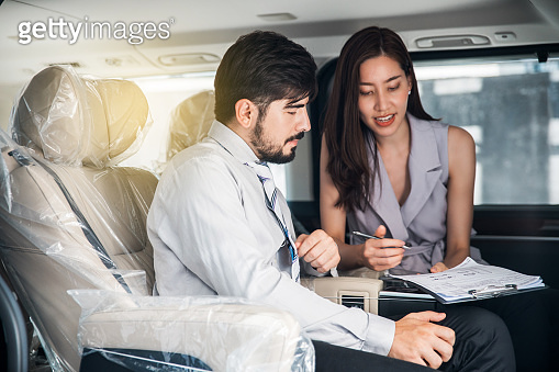Car Dealership. The Asian Salesman (woman) checking the list with the middle east customer inside the new car with plastic wrapped seats before hand over. Automotive Leasing and Dealing Business.