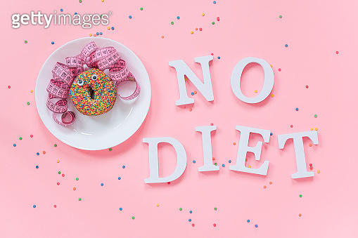 Abstract funny face of woman from donut with eyes and hair from centimeter tape on plate and text No diet on pink background. Concept International No Diet Day, 6 may Top view Flat lay