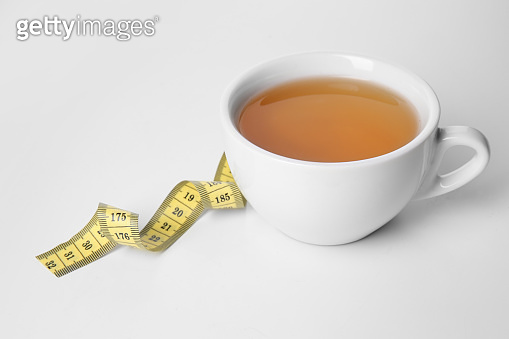 Cup of tea with measuring tape on white background. Weight loss concept