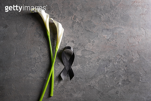 Black funeral ribbon and flowers on grey background