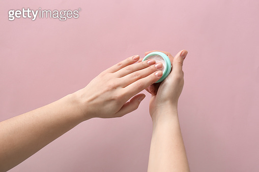 Female hands with jar of natural cream on color background