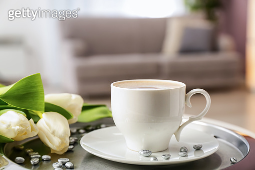 Tray with cup of coffee and beautiful flowers on table
