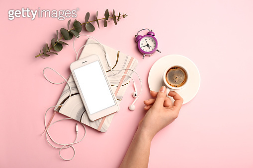 Female hand with cup of coffee, mobile phone, notebook and clock on color background