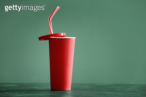 Paper cup of tasty soda on color table