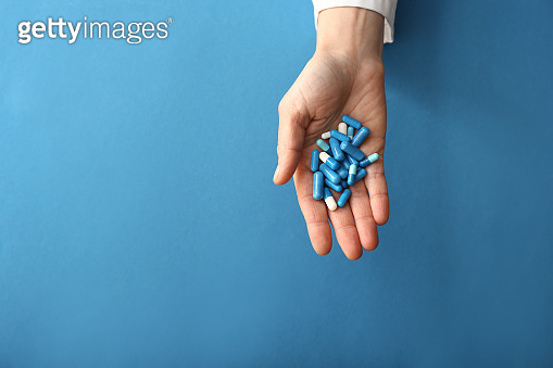 Female hand with pills on color background
