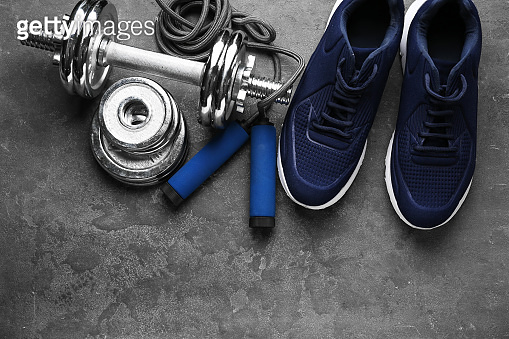 Shoes and sport equipment on grey background