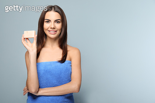 Beautiful young woman with soap on color background