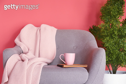 Cup of hot tea and plaid on armchair