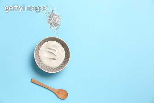 Cosmetic clay with spoon on color background
