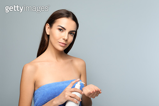 Beautiful young woman with bottle of liquid soap on color background