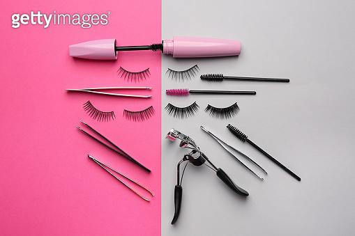 Mascara with false eyelashes and tools on color background
