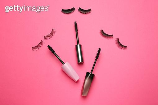 Mascara with false eyelashes on color background