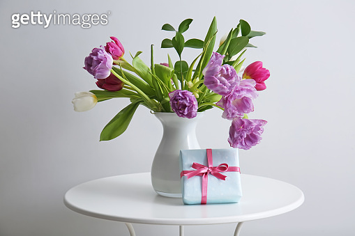 Bouquet of beautiful flowers with gift box on table against light background
