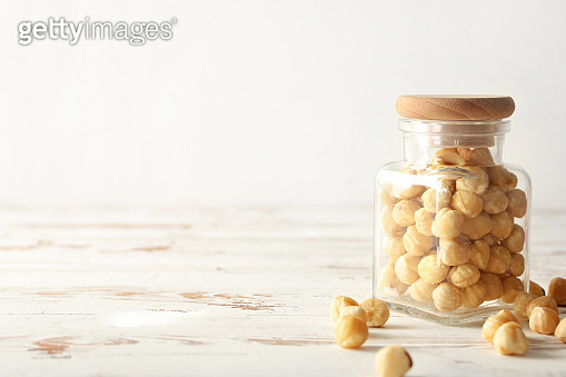 Jar with tasty hazelnuts on wooden table