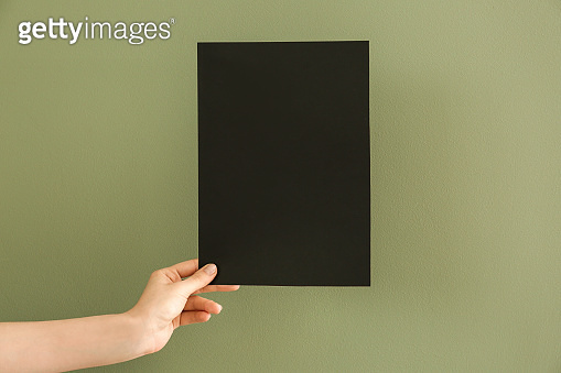 Female hand with blank invitation card on color background