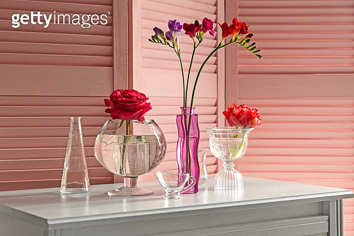 Glass vases with beautiful flowers on table