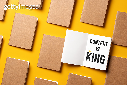 content is king for online marketing concept.top view of open notebook with golden crown align with kraft paper book in pattern on yellow table background